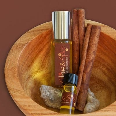 citrus-and-spice™ natural botanical perfume sampler and roll-on bottle in wooden bowl with cinnamon sticks and frankincense resin | Photo Copyright © Cynthe Brush www.essentialoilsforhealing.com www.gaiaspharmacopeia.com www.gaiaspharmacy.com