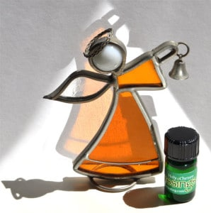 9 blessings holy chrism™ essential oils bottle near stained glass angel in sunlight | Photo Copyright © Cynthe Brush www.essentialoilsforhealing.com www.gaiaspharmacopeia.com www.gaiaspharmacy.com