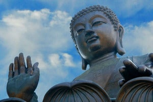 buddha statue with raised hand in blessing gesture seen against the sky